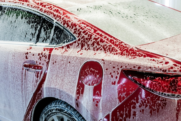 Washing red car with active foam at car wash service.