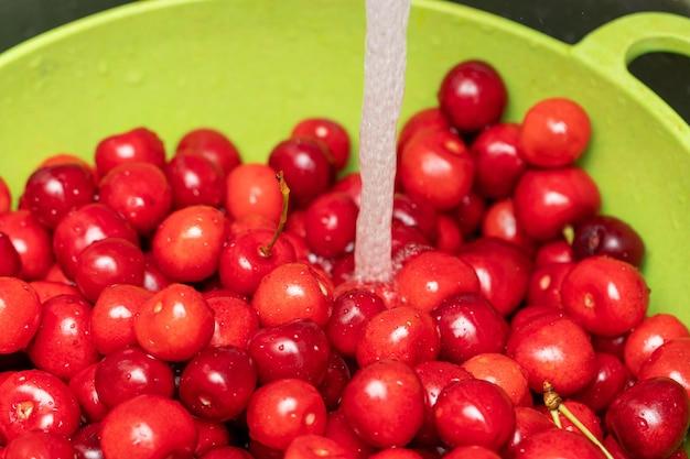녹색 그릇에 있는 수돗물 아래 빨간 달콤한 체리를 씻고 소쿠리를 닫습니다