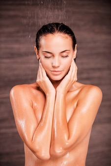 Washing stress away. beautiful young shirtless woman standing in shower and keeping eyes closed
