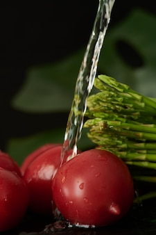トマトとアスパラガスを水の流れで洗い、野菜の蛇口から水を注ぐ