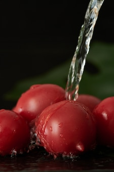 Washing tomato with a stream of water, pouring water from the tap on the vegetables