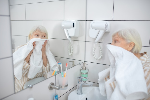 Washing up. gray-haired woman drying her face with the towel