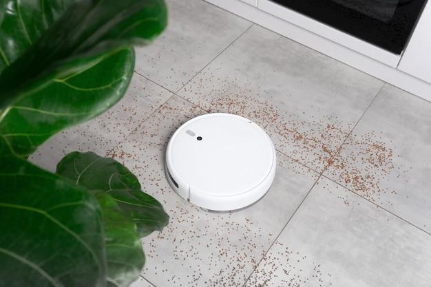 Мойка белый робот пылесос устройство уборки пола от крошек крупы дома на утонитовой плитке на кухне.
