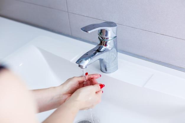 욕실의 수도꼭지 아래 흐르는 물로 여성의 손을 씻고, 바가 있는 흰색 세면대에서 손을 씻고, 위생, 손 씻기, 수돗물로 손을 씻는 여성