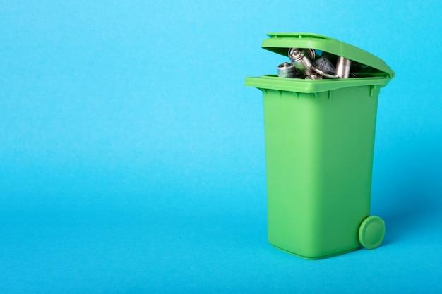 プラスチック容器に電池を廃棄します。廃棄物のリサイクル。環境の概念。青い背景の電池とバスケット。