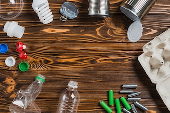 Waste items on brown wooden textured background with space for text
