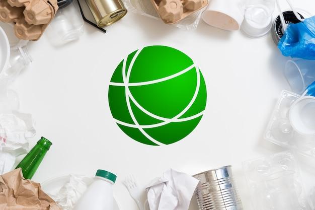 Управление отходами и сортировка. защита окружающей среды. пластик, бумага, стекло, металлический мусор расположены вокруг зеленого символа.