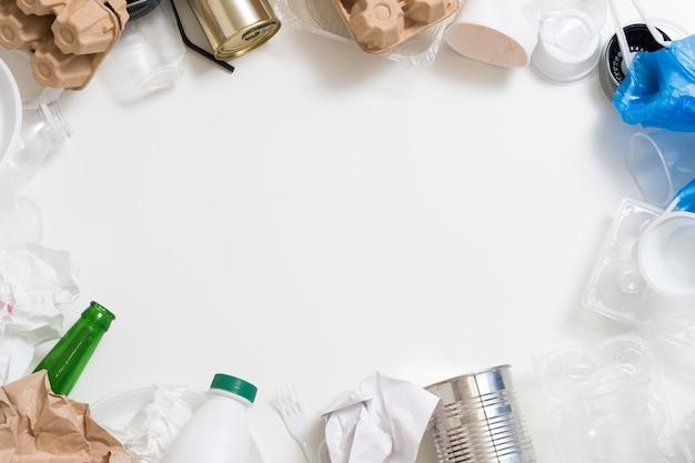 Управление отходами и сортировка. пластик, бумага, стекло, металлический мусор обрамляют овальное пространство копии в центре.