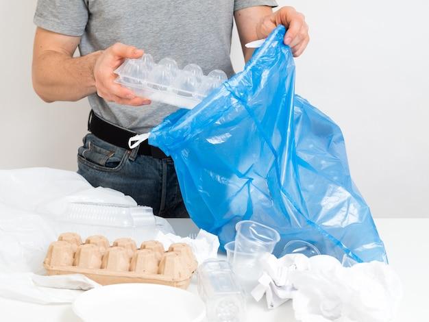 Управление отходами, сортировка, переработка. мужчина собирает одноразовый мусор в полиэтиленовый пакет.