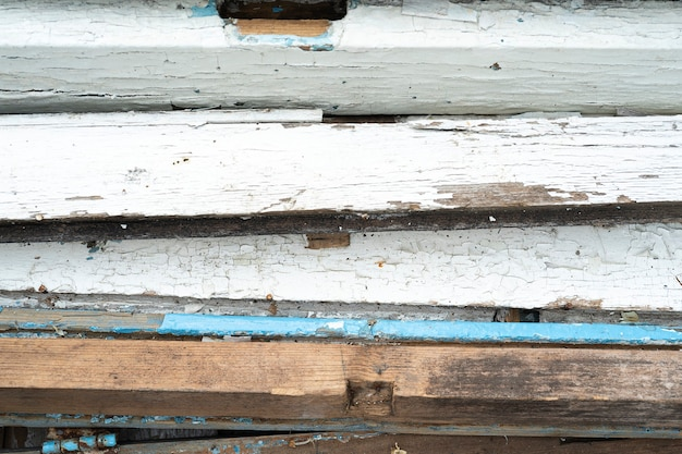 裏庭のデッキを解体し、削除する古い塗装された木製の山の背景とテクスチャを無駄にする