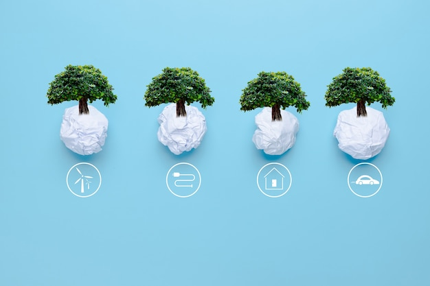 Waste paper with big tree on blue background with icons energy sources for renewable, solar cells energy, sustainable development. ecology and environment concept.