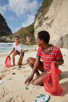 Waste problems concept. diverse tourists clean beach from rubbish
