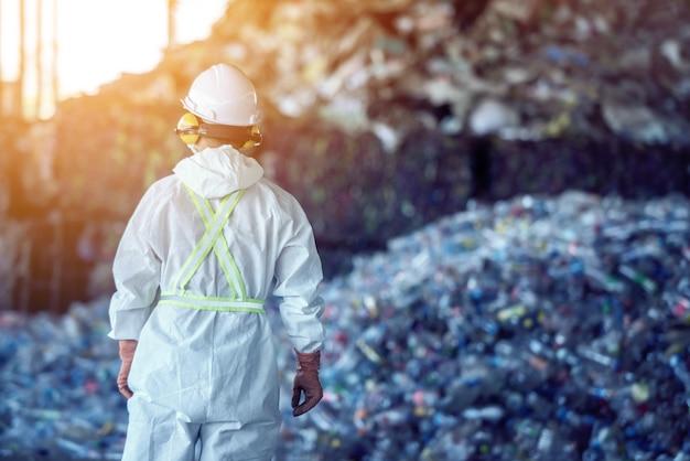 廃棄物処理プラント。加工とリサイクルのための工場での技術的プロセスのペットボトル。労働者のリサイクル工場、エンジニアは焦点が合っていないか、ぼやけています。