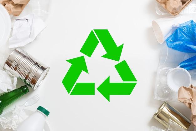 Сортировка и переработка мусора. пластик, бумага, стекло, металлический мусор на белом фоне. зеленый символ в центре.