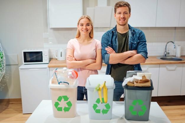 집에서의 폐기물 분류. 환경을 보호하다. 부엌에서 녹색 재활용 아이콘으로 다채로운 쓰레기통에 폐기물을 넣어 젊은 행복한 가족