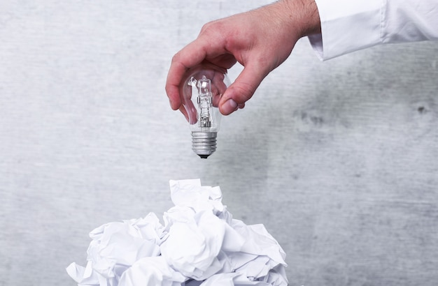 Wasted papers in the garbage bin with a bulb
