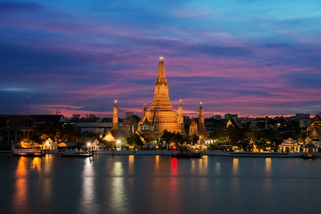Wat arun temple and chao phraya river at night in bangkok, thailand