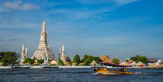 Wat arun temple with river and transportation boat in bangkok city