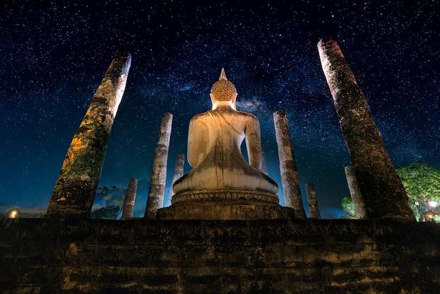 Млечный путь над большим буддой ночью в храме wat mahathat, sukhothai исторический парк, таиланд.