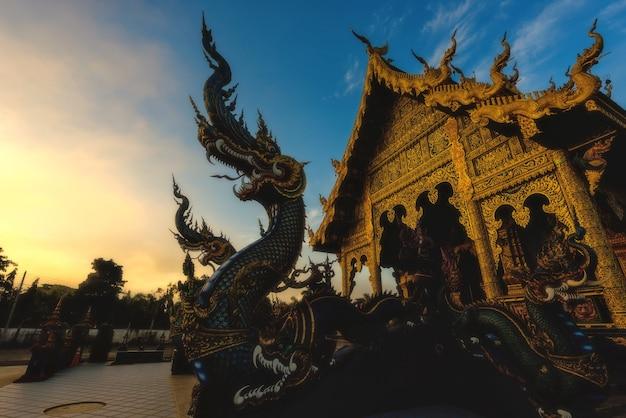 タイ、チェンライの夕暮れの夜明けにナーガドラゴンの彫刻があるワットロンスアテン寺院の入り口。美しい伝統芸術のデザインを見るための有名な旅行先。