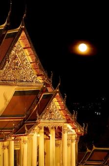 Wat suthat thepwararam buddhist temple with the bright full moon bangkok old city thailand