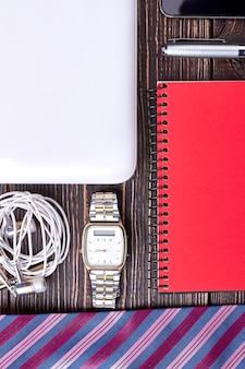Часы и наушники по дереву. блокнот и галстук. бизнес и технологии.