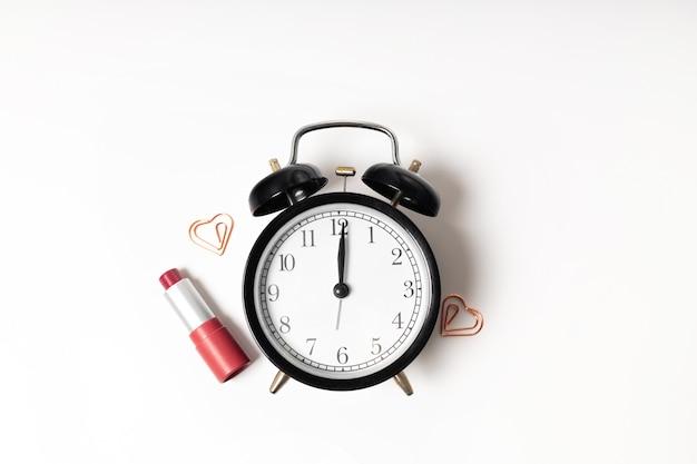 시계와 흰색 표면에 립스틱