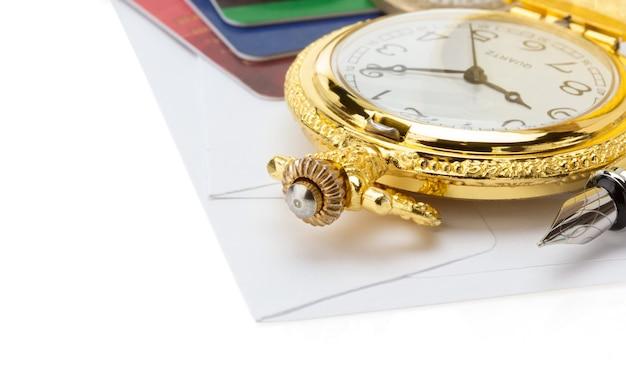 白い背景で隔離の封筒で時計とペン