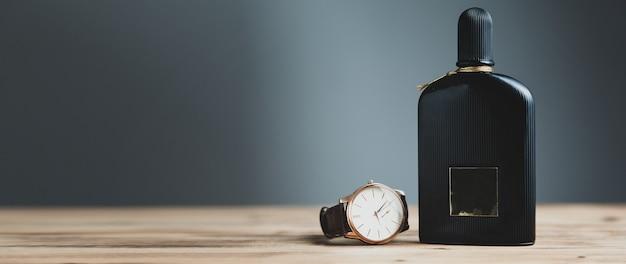 Часы и флакон духов на столе