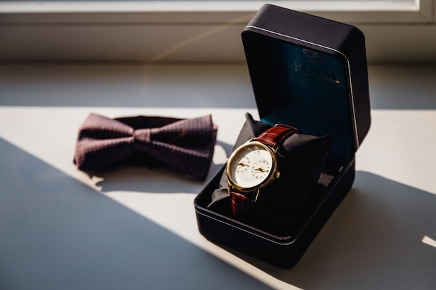 Watch in black box and a bow tie lie on the white windowsill