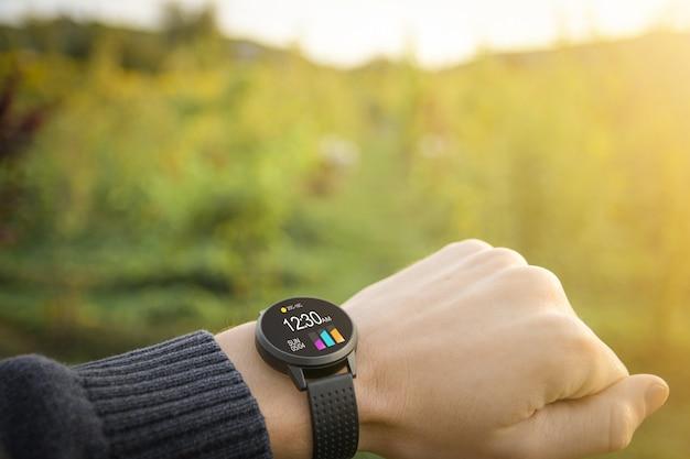 시계, 기본 기능의 아이콘으로 흐린 녹색 자연에 야외에서 손에 피트니스 트래커 건강을 확인하는 기술의 개념. 확대