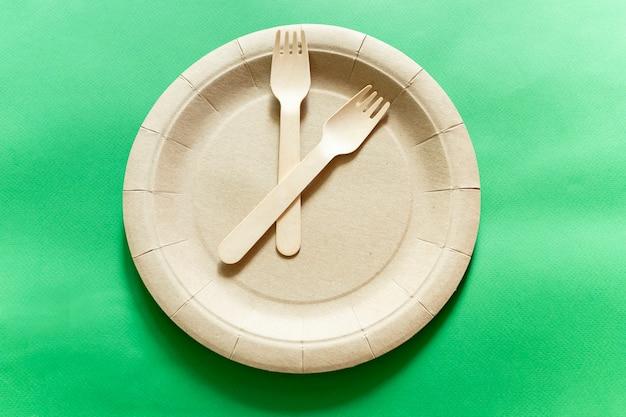Часы из экологически чистой одноразовой посуды из бамбукового дерева и бумаги на зеленом фоне.