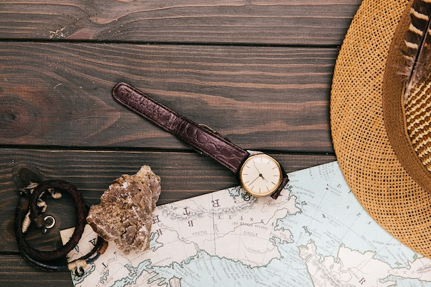 Watch, hat and stone lie on tavel map