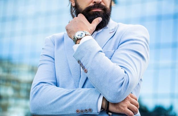 男を見てください。ビジネスマンは町の彼の時計を指しています。男は時計を持っている。ビジネススーツで成功した実業家の肖像画、