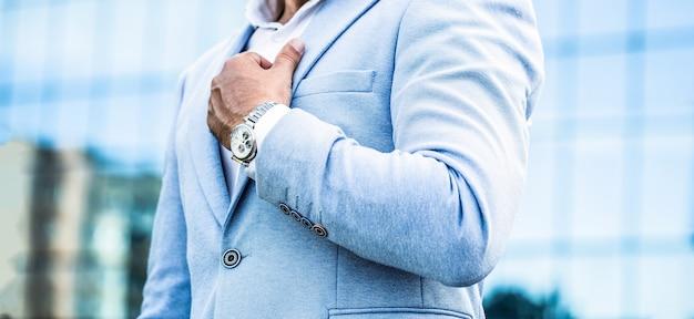 男を見てください。ビジネスマンは町の背景に彼の時計を指しています。