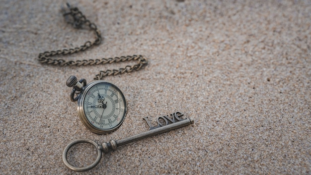 Watch necklace and key on sea beach