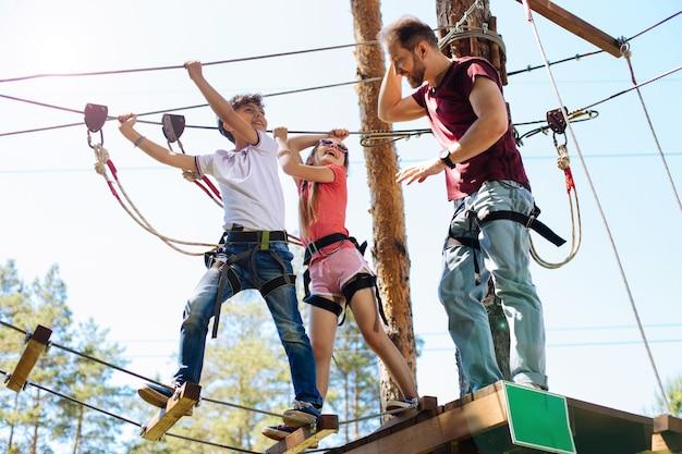 Осторожно. заботливый молодой отец инструктирует своих детей о безопасности в веревочном парке перед тем, как начать спуск по тропам веревочного парка