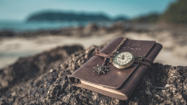Watch pendant on brown leather notebook