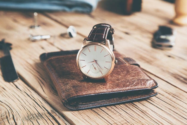 Watch on wallet on the wooden desk