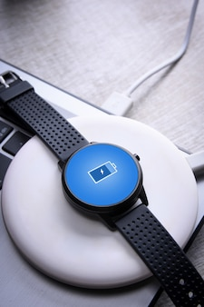 Watch on wireless charging with on-screen charging indicator. at the desktop, near the laptop. top view. place for text