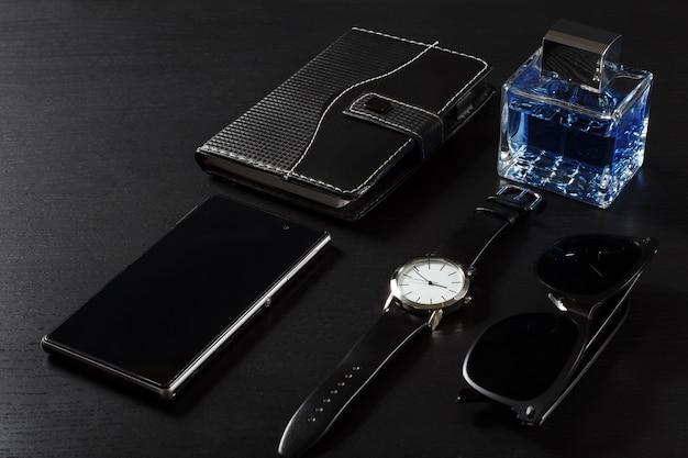 革のストラップ、革のカバーのノートブック、携帯電話、男の香水、黒い背景のサングラスで見る
