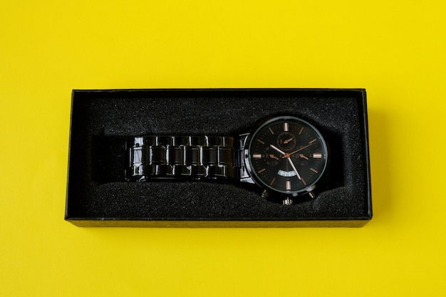 Watch, with black cardboard isolated on yellow background