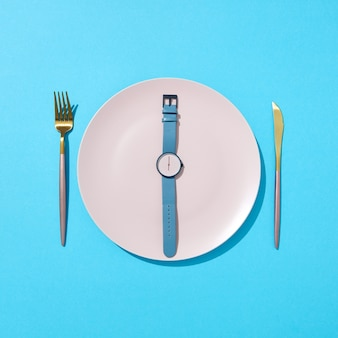 Watch with time six o'clock on a white plate with knife and fork on a blue wall, place for text. concept of limiting the intake of food diet and weight loss. flat lay.