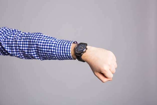 Watch on wrist isolated over a gray wall.