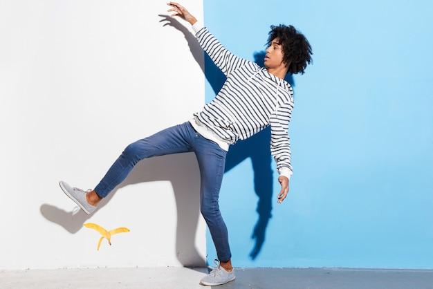 Следи за своим шагом! красивый молодой африканский человек, скользящий на красочном фоне