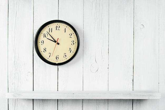 時計と木製の棚。白い、木製の背景に。