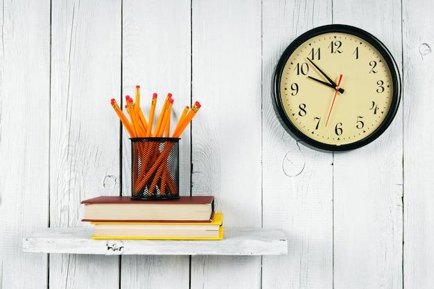 나무 선반에 시계, 책 및 학교 도구. 흰색, 목조 배경.
