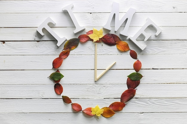 Часы из листьев на белом деревянном фоне