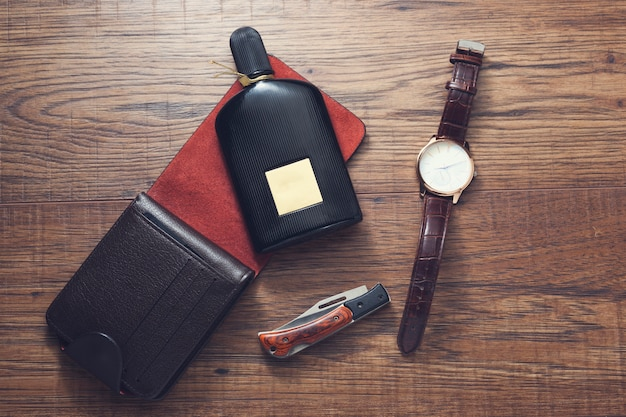 Watches, wallet and perfume on wooden table