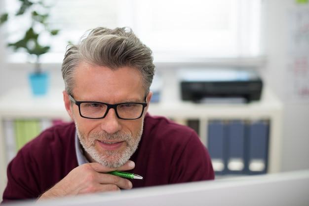 オフィスでコンピューターを使用している用心深い男